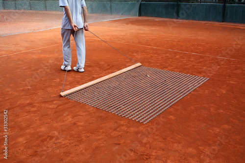 man cleaning tennis court