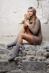 sexy girl with teddy bear sitting on wall