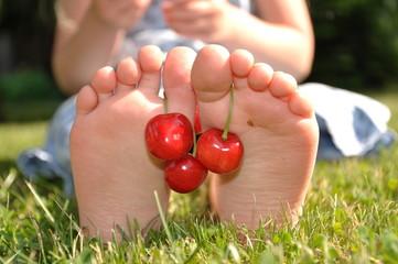 Füße mit Kirschen geschmückt.
