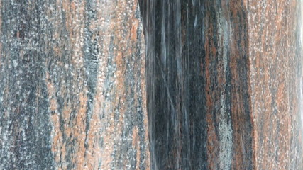 Close up of water running down a red granite rock.