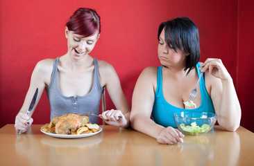 Tailored diet. Skinny woman whole chicken,overweight small salad