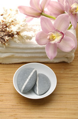 Bowl of zen stones with pink orchid over mat