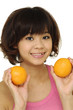 Beautiful young woman holding an orange-.Close up