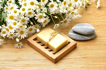 White flower with zen stone on woven mat