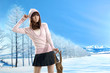 attractive woman dressed in winter clothes in a winter park