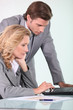 businessman and businesswoman looking at laptop