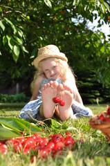 Mädchen schmückt  Füße mit frischen Kirschen.