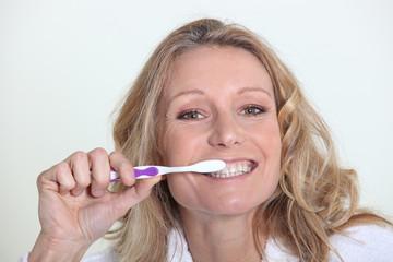 45 years old blonde woman is brushing her teeth