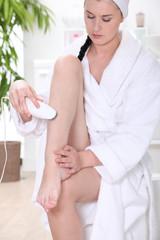 Woman epilating leg