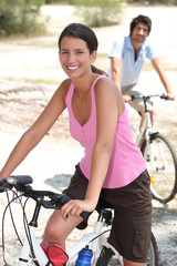 Couple riding bicycles through the countryside