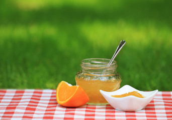 Jar of orange jam in the summer garden