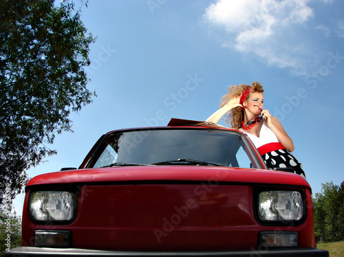 Girl in dress with red comapct car - 33313320