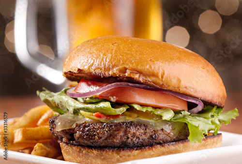 Staande foto Assortiment gourmet cheeseburger with mug of beer in background