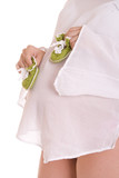 Pregnant woman, holding olive-colored booties around the abdomen poster