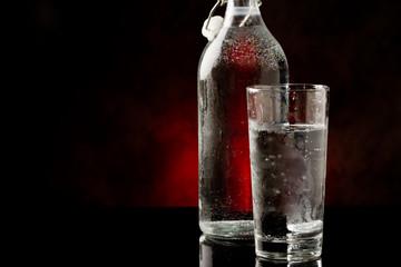 Acqua in bicchiere di vetro con bottiglia