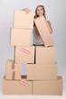 Young woman with a pile of cardboard boxes marked fragile