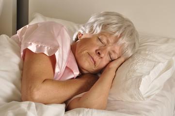 Seniorin schläft in einem Bett