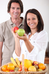 Man and woman with a basket of fresh fruit