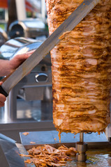 Chef slicing Turkish doner kebab.