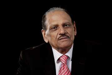 Senior indian man in business suit, on black background