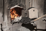 Throw more charcoal on the fire in open iron stove - 33335341