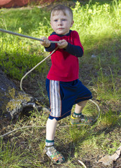 Little boy pulls the rope by hand