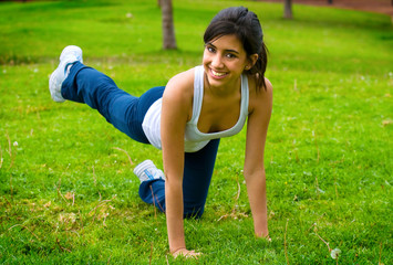 Young woman exercising legs on the grass