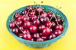 studio shot of a  basket  with cherries on a yellow tablecloth