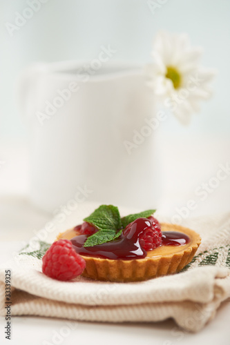 raspberry tart on a napkin, in background white flower