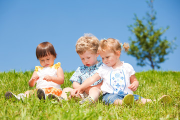 Kids sit on grass