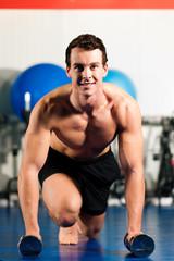 Mann macht Liegestütze im Fitnessstudio