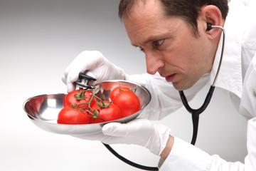 Arzt untersucht Tomaten mit Stethoskop auf Gefahr für Gesundheit
