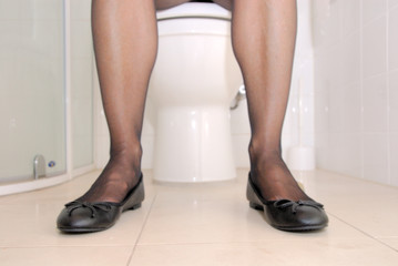 Frau sitzt auf einer Toilette