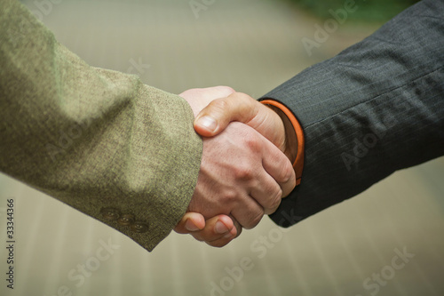 Businesspeople shaking hands, making an agreement.