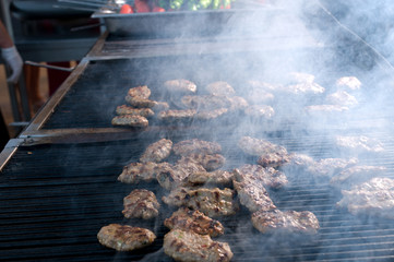 Grilled meatballs on barbecue smoking.