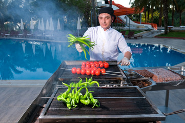 Chef cooking meatballs on barbecue.
