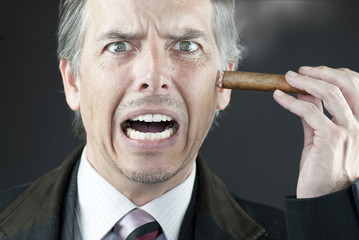 Stressed Businessman Stubs Out Cigar On Face