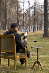 uomo in mezzo al bosco con bottiglia di vino