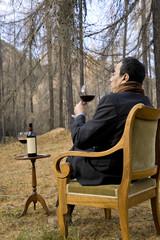 uomo seduto su una poltrona nel bosco bevendo vino