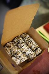 Inside out sushi rolls with sesame seeds in the box