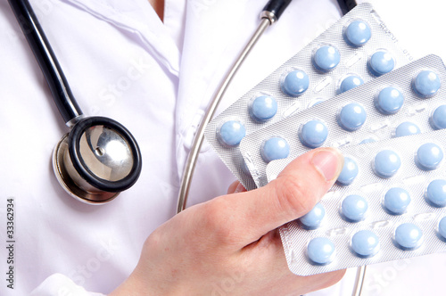 Close-up of a doctor showing three packs of blue pills