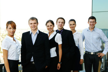 Six young businesspersons in formal clothes standing in a row