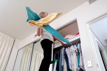 Frau schmeisst lustlos Kleidung in den Schrank