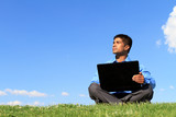 businessman sitting down with laptop and looking at the sky