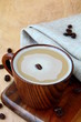 coffee cappuccino in a stylish wooden cup with coffee beans