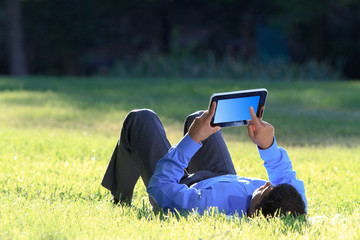 businessman working with digital tablet at the park