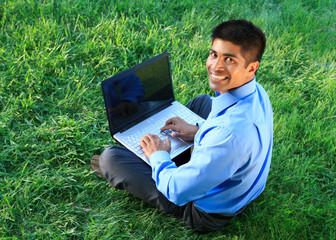 smiling businessman with laptop at the park