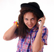 A funny young girl tries on an old black hat