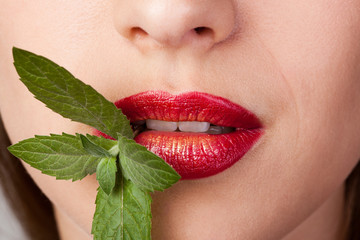 Closeup of lips with red lipstick and gold holding peppermint