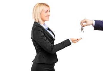 A blond businesswoman taking keys from a businessman